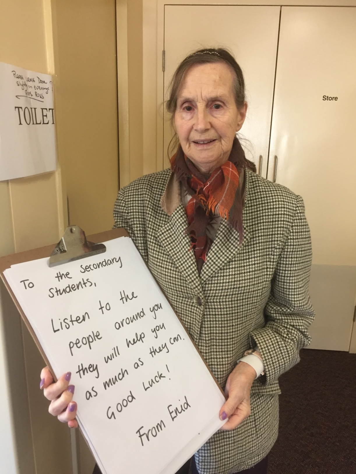 """Enid, a resident, holds up a large clipboard with a hand written message which reads: """"To the Secondary Students, Listen to the people around you, they will help you as much as they can. Good luck! From Enid."""""""